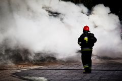 Firefighters fighting a fire of a waste place Stock Image