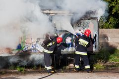 Firefighters fighting a fire of a waste place Royalty Free Stock Images
