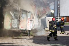 Firefighters fighting a fire of a waste place Stock Photos