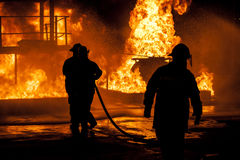 Firefighters fighting fire. With water Stock Photo