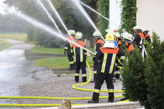 Firefighters firemen extinguishing fire in operation Royalty Free Stock Images