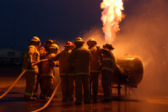 Firefighters and flames. Firefighters training on flaming propane prop Royalty Free Stock Photography