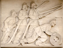 Firefighters frieze, London. Art Deco bas relief sculpture showing fire fighters directing hoses at a blaze.  On public display since 1937, sculpted by Gilbert Royalty Free Stock Images