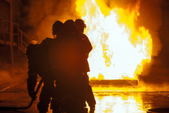 Firefighters in front of burning tank during firefighting exercise Stock Image