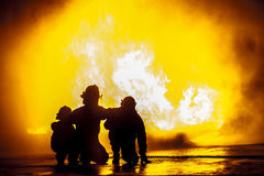 Firefighters in front of a burning tank Stock Photos
