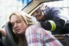 Firefighters helping an injured woman in a car royalty free stock photos