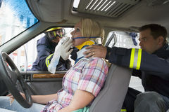 Firefighters helping an injured woman in a car stock image