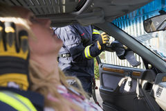 Firefighters helping an injured woman in a car stock photos