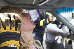 Firefighters helping an injured woman in a car royalty free stock image