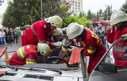 Firefighters helping victim. Firefighters helping wounded young man in car accident. Photo taken during an exercise Stock Photos