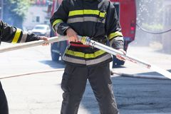 Firefighters holding firehose to extinguish fire stock photography