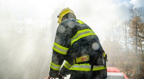 Firefighters with a hose in action. Firefighters with a hose to save property and life Stock Photo