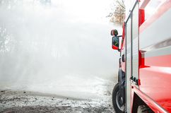 Firefighters with a hose in action. Firefighters with a hose to save property and life Stock Images