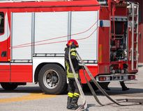 Firefighters with the hose to put out the fires and the firetruc Royalty Free Stock Photography