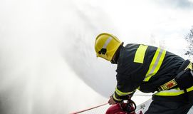 Firefighters with a hose in action. Firefighters with a hose to save property and life Stock Photography