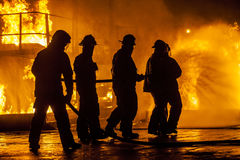 Firefighters hosing down fire Stock Photos