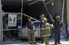 Firefighters inspect a car that drove thru a store royalty free stock photography