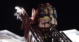 Firefighters ladder climb on roof. Firefighters ladder climb on roof with axe. Truck with ladder engin stock footage
