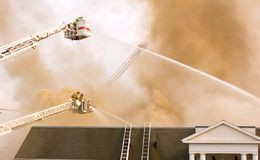 Firefighters on ladder platform. Firefighters on tower ladder shooting water on roof of burning building Stock Photography