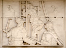 Firefighters on ladders sculpture. Art Deco bas relief sculpture showing fire fighters directing hoses at a blaze.  On public display since 1937, sculpted by Stock Photography