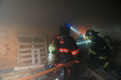Firefighters at Live Burn Training. Firefighters battle a fire inside a burning farm house during a live burn training in Berlin Vermont. Live Burn trainings Stock Photography