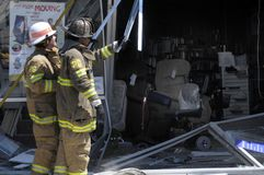 Firefighters look at damage done when a car drove into a medical supply store in. Firefighters inspect damage done when a car drove into a medical supply store stock photos