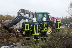 Firefighters next to ruins of a fully burned farm, where died more than 30 cows, 23.10.2018, in Koknese, Latvia. Ruins of a fully burned farm, where died more stock photo