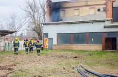 Firefighters are oversees burning industrial building, ready for stock photography