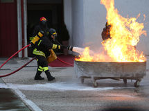 Firefighters with oxygen tank extinguishing a fire with foam Stock Image