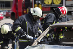 Firefighters with the pneumatic shears open the car doors Stock Images