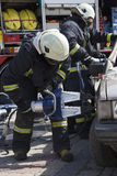 Firefighters with the pneumatic shears open the car doors Royalty Free Stock Photos