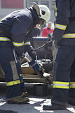 Firefighters with the pneumatic shears open the car doors Royalty Free Stock Images