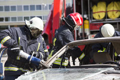 Firefighters with the pneumatic shears open the car doors Royalty Free Stock Photo