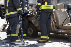Firefighters with the pneumatic shears open the car doors Stock Image