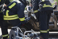 Firefighters with the pneumatic shears open the car doors Royalty Free Stock Photography