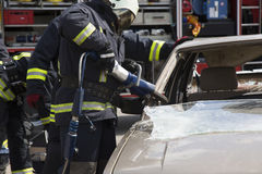 Firefighters with the pneumatic shears open the car doors Stock Photography