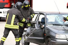 Firefighters with pneumatic shears open the car doors Stock Photos