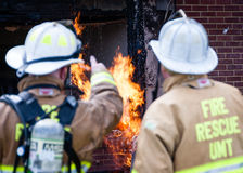 Firefighters pointing to flame. Firefighters, fire chiefs pointing to flame, apartment structure fire Royalty Free Stock Photos