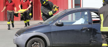 Firefighters during a practice of traffic accident simulation Stock Image