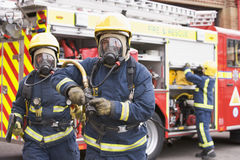 Firefighters in protective workwear. By fire engine Royalty Free Stock Image