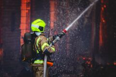 Free Firefighters Put Out Large Massive Fire Blaze, Group Of Fire Men In Uniform During Fire Fighting Operation In The City Streets, Royalty Free Stock Photography - 216897207