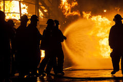 Firefighters putting out burning structure with water Royalty Free Stock Photos