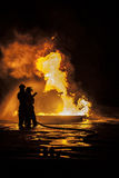 Firefighters putting out a fire. On a burning fuel tank Stock Photo