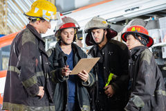 Firefighters Reading Clipboard At Fire Station Royalty Free Stock Photo