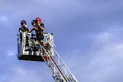 Firefighters on rear platform. Three firefighters on top of an extended rear platform during the celbration of the Virgin Mary La Paloma who is the patron saint Stock Images