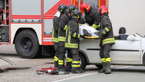 Firefighters relieve an injured after car accident Stock Images