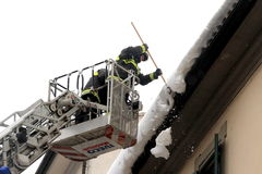 Firefighters remove snow from the eaves Royalty Free Stock Photo