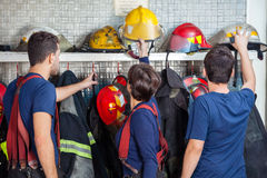 Firefighters Removing Helmets From Shelf Royalty Free Stock Photography