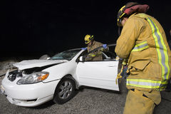Firefighters At The Rescue. Firefighters at the site of car accident Stock Image