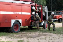 Firefighters run out of the fire engine stock photography